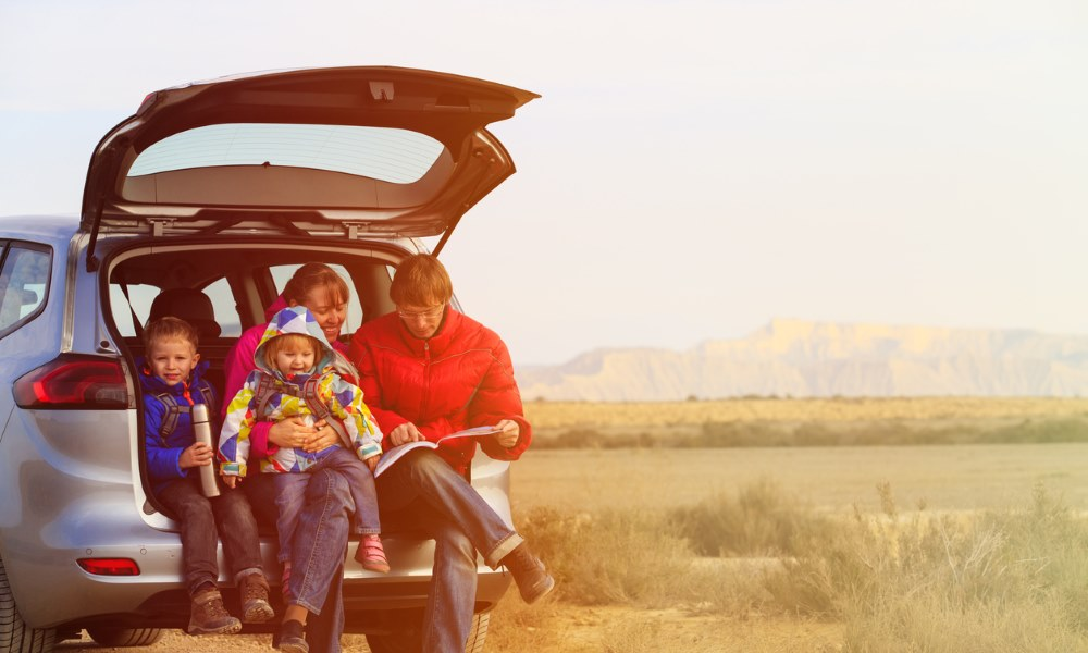family sitting in boot of a car outdoors